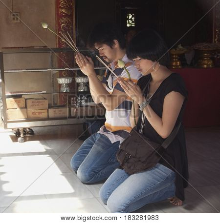 Asian couple praying at temple
