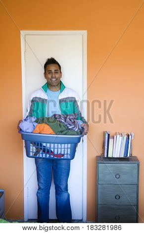 Mixed race man carrying laundry basket