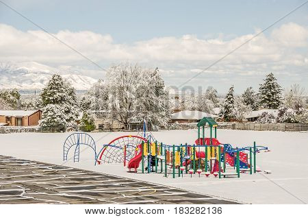 Brightly colored playground equipment stands out in the snow