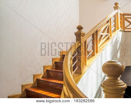 Wooden stairway with handrail and stainless banister white wall modern home interior.