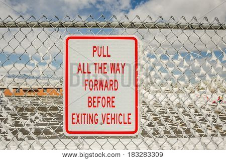 Sign telling motorists to pull all the way forward before exiting vehicle