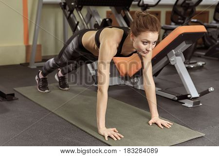 Slim fitnes young girl with ponytail doing planking exercise in the gym.