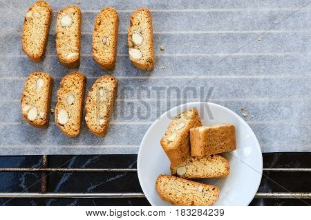 Baking tray with fresh baked biscotti cantuccini or cantucci Italian almond sweets biscuits (cookies) traditionally served with a drink coffee or vine. Copy space.Top view.