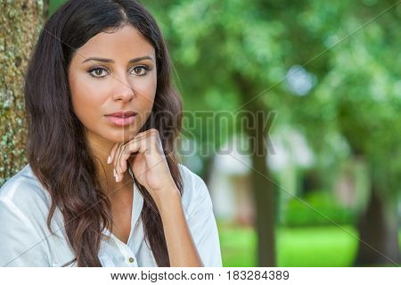Outdoor portrait of a beautiful thoughtful young female Latina Hispanic woman