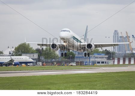 Commercial jet airliner airplane landing on the runway of a busy modern airport