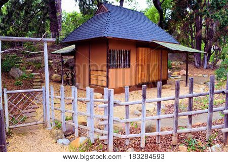 Japanese style Teahouse surrounded by a rustic wooden fence and a forest taken in a meditation garden