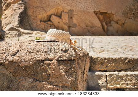 Tourist's Hat On Rang Of Old Stone Wall Of Santa Barbara Castle In Alicante, Valencia Provense, Spai