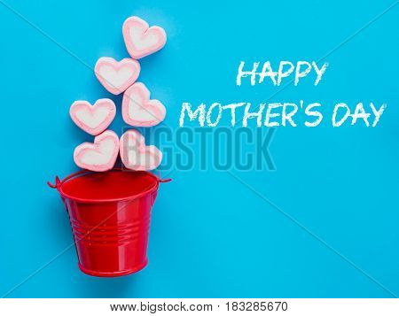 mother's day concept. Marshmallow in a red bucket with Happy mother's day text on blue sky background