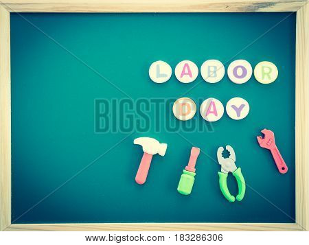 Labor day background concept - Happy labor day text with tools toy on greenboard background top view