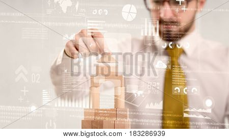 Young handsome businessman using wooden building blocks with mixed data around him