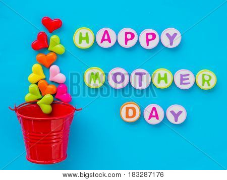 mother's day concept. HAPPY MOTHER DAY alphabet with colorful heart and red bucket on blue background