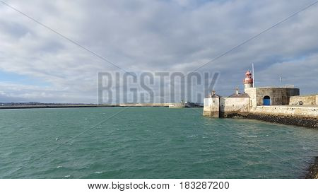 Clouded sky and view of an irish harbor with ancient lighthouse