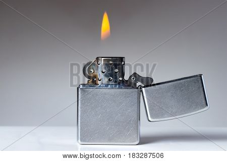 Cigarette lighter with flame on white and grey background. Nicotine and tobacco addiction abstract concept. Copy space on the left.