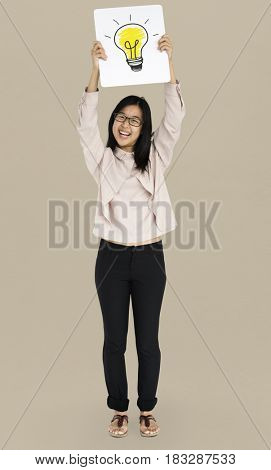 Young adult asian girl smiling and holding light bulb banner