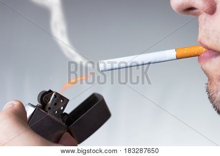 Young man smoking cigarette with classic old scratched lighter. Nicotine and tobacco addiction abstract concept.