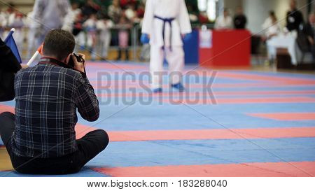 Photographers shoot during a karate competitions, telephoto