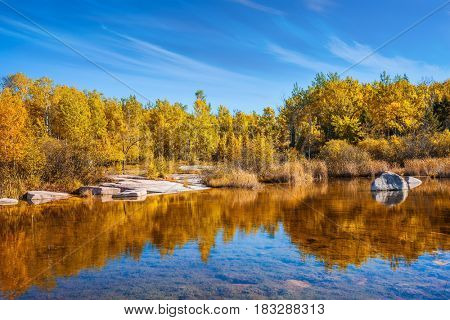 The Winnipeg River. Yellow autumn grass is reflected in the smooth water surface. Old Pinawa Dam Provincial Heritage Park. The concept of travel