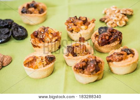 Small portioned tartlet cakes with filling of nuts and dried fruits. Professional baking. Background -prune