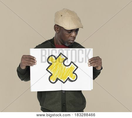 African man holding placard with jigsaw piece icon