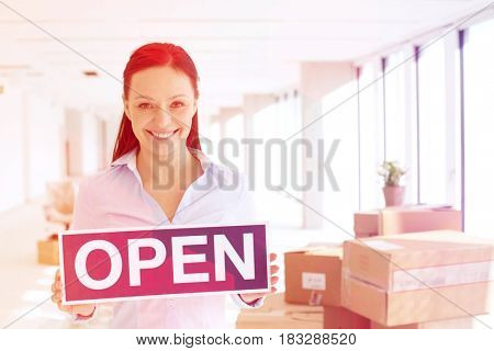 Portrait of smiling mid adult businesswoman holding open sign in new office