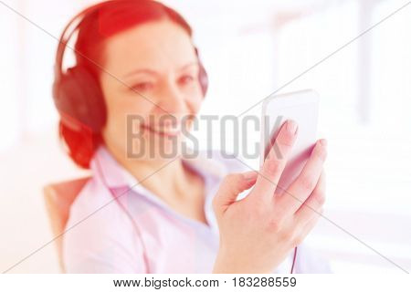 Smiling businesswoman listening music through smart phone in office