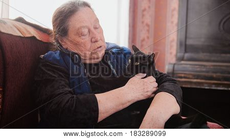 Portrait of old lady at home - senior woman sits on sofa with black cat - close up, telephoto