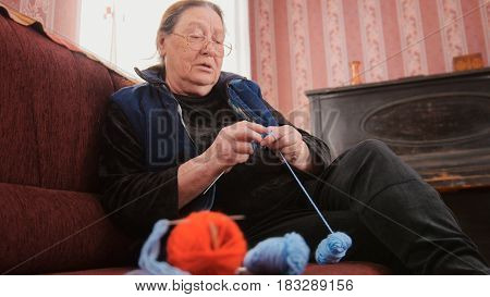 Old woman pensioner home - knits wool socks sitting on the sofa - elderly lady hobby, bottom view
