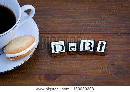 Debt text on a wooden background. Coffee mug with a tasty biscuit