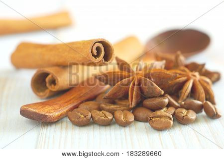Coffee grains with anise star, wooden old-style spoon and cinnamon sticks on vintage wooden table food ingredients background. Selective focus. Cappucino ingredients food backdrop.
