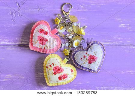 Beautiful hearts and flowers keyring. Handmade felt and fabric keyring or bag charm isolated on lilac wooden background with copy space for text