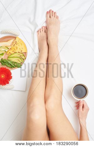 Flat lay of relaxing wonderful girl enjoying romantic breakfast with fresh-brewed tea, avocado and cheese