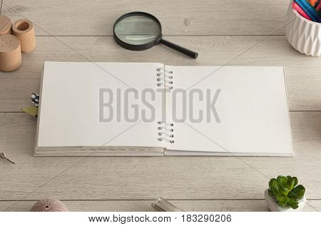 Empty notebook on wood floor with office tools nearby