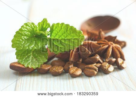 Fresh spearmint leaves, wooden spoon with coffee grains and anise spice star on retro wooden table food background. Selective focus. Aroma spicy caffeine drink ingredients.
