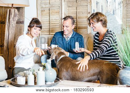 Young couple with dog sitting on sofa and having tea with friend at home.
