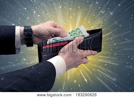 Businessman hand takes out dollar from wallet with fireworks and grungy background