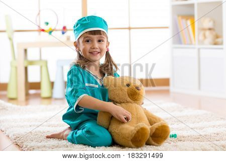 Four years old girl plays doctor with plush toy in the nursery