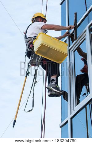 window washer working  at building outdoor hanging on rope