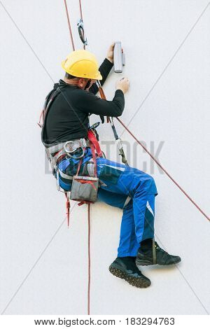 professional electrician worker repairs a light on the building hanging on rope