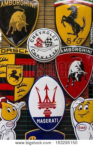 BERLIN - JUNE 14 2015: Background of various emblems of various car brands producing sports cars. The Classic Days on Kurfuerstendamm.