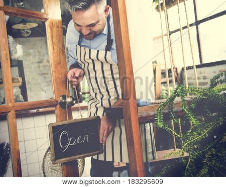 Man Hanging Open Sign by the Glass Window