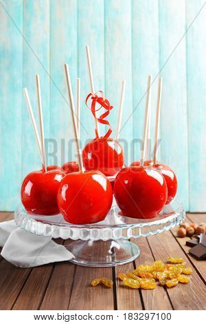 Delicious toffee apples on glass stand against wooden background