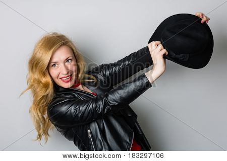Beautiful woman in a jacket with a black hat against the wall