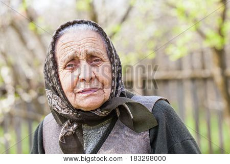 Portrait of a happy senior woman posing at home on spring time