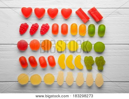 Composition of colorful jelly candies on light wooden background