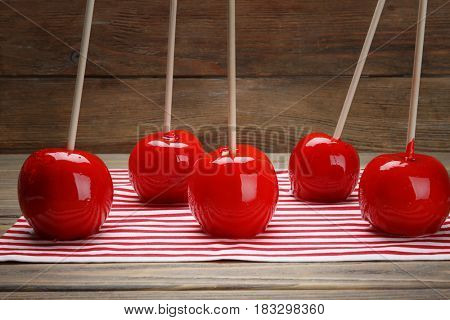 Delicious holiday apples on striped towel against wooden background