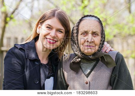 Picture of a sick elderly woman posing with her happy caretaker outdoor