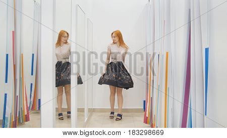 Young woman trying dress near mirror in fitting room - shopping concept, horizontal