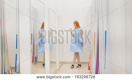Young woman trying blue dress near mirror in fitting room at store, middle shot