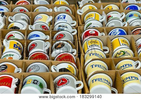 BERLIN - JUNE 14 2015: Background of enamel mugs with logos of automobile firms. The Classic Days on Kurfuerstendamm.