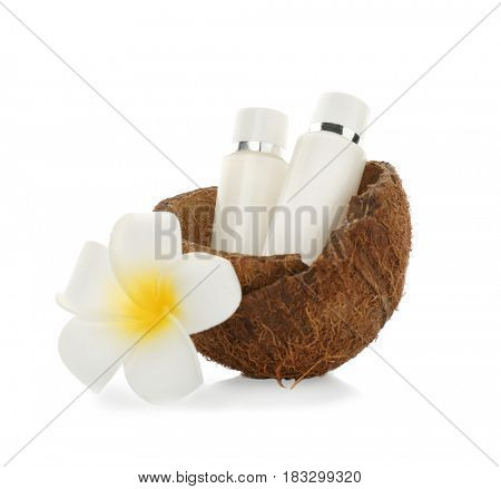 Bottles with cream in coconut rind and tropical flower on white background